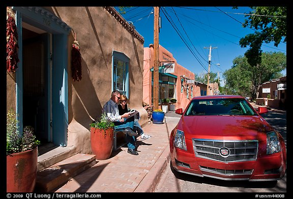 Couple reading art magazine in front of gallery. Santa Fe, New Mexico, USA (color)