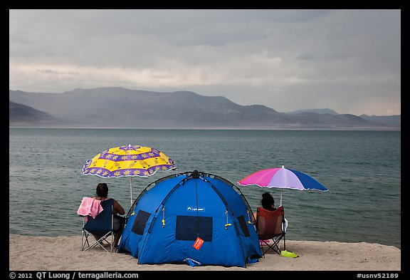 People with tent and beach umbrellas, approaching storm. Pyramid Lake, Nevada, USA (color)