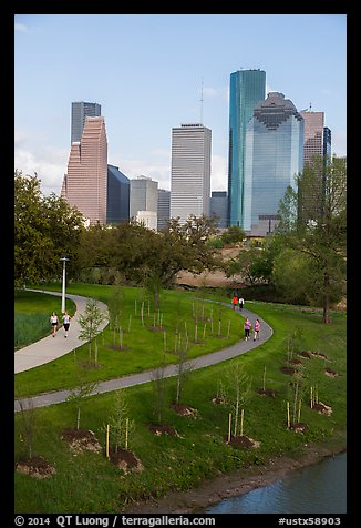People walking in park with skyline behind. Houston, Texas, USA (color)