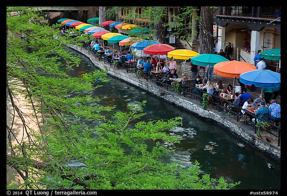 Tables under colorful umbrellas next to canal. San Antonio, Texas, USA (color)