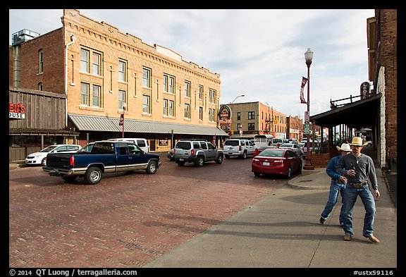 Stokyards street with brick buildings, men with cowboy hats. Fort Worth, Texas, USA (color)
