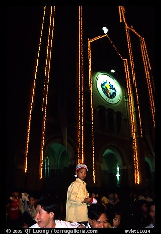 Child with christmas hat in front of St Joseph Cathedral on Christmas eve. Ho Chi Minh City, Vietnam (color)