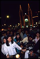 Women on motorbike in front of St Joseph Cathedral on Christmas eve. Ho Chi Minh City, Vietnam ( color)