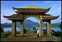 Pagoda gate with woman standing near lake. Da Lat, Vietnam
