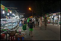Shoppers walk past craft booth at night market. Phu Quoc Island, Vietnam ( color)