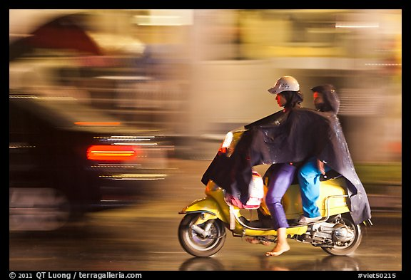 Women riding scooter in the rain. Ho Chi Minh City, Vietnam (color)