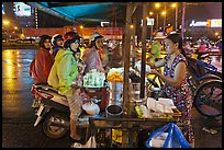 Women riding motorbikes buy sweet rice. Ho Chi Minh City, Vietnam (color)