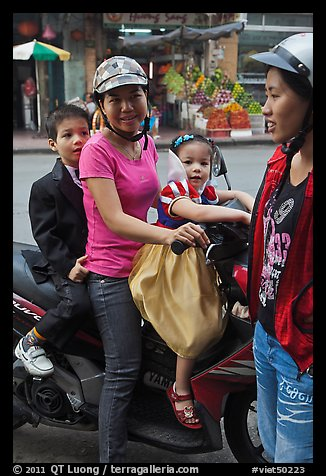 Woman riding with children. Ho Chi Minh City, Vietnam (color)