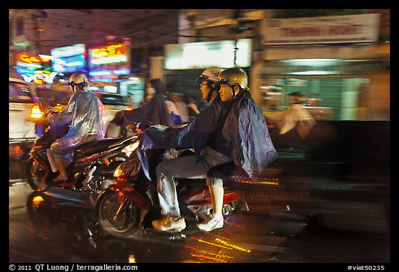 Motorcyle riders at night, dressed for the rain. Ho Chi Minh City, Vietnam (color)