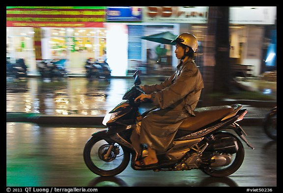 Riding motorcyle on rainy night. Ho Chi Minh City, Vietnam (color)