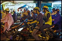 Street crowded with motorcycles on rainy night. Ho Chi Minh City, Vietnam (color)