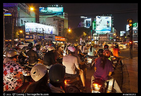 Motorbikes waiting at traffic light at night. Ho Chi Minh City, Vietnam (color)
