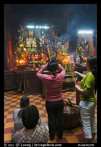 Women offering incense to Jade Emperor figure, Phuoc Hai Tu pagoda, district 3. Ho Chi Minh City, Vietnam (color)