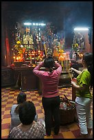 Women offering incense to Jade Emperor figure, Phuoc Hai Tu pagoda, district 3. Ho Chi Minh City, Vietnam