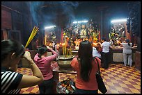 Worshipping at altar with  Jade Emperor and Four Big Diamonds, Chua Ngoc Hoang, district 3. Ho Chi Minh City, Vietnam (color)