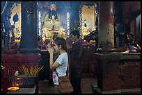 Couple worshipping Thang Hoang, Chua Ngoc Hoang pagoda, district 3. Ho Chi Minh City, Vietnam (color)