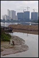 Man wading in mud, with background of towers in construction, Phu My Hung, district 7. Ho Chi Minh City, Vietnam ( color)