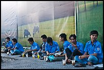 Uniformed students sitting in front of backdrops depicting traditional landscapes. Ho Chi Minh City, Vietnam