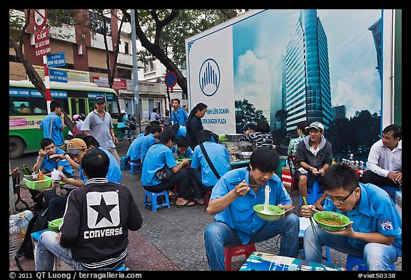 Uniformed students eating breakfast in front of backdrop depicting high rise in construction. Ho Chi Minh City, Vietnam (color)