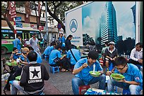 Uniformed students eating breakfast in front of backdrop depicting high rise in construction. Ho Chi Minh City, Vietnam