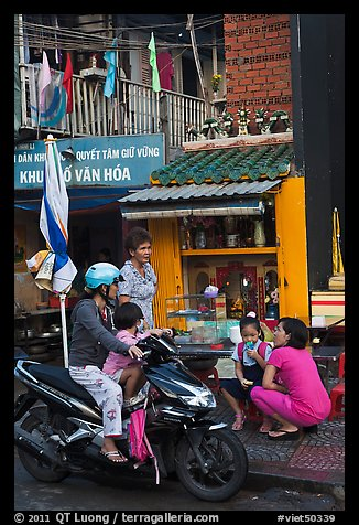Neighborhood chat in front of street altar. Ho Chi Minh City, Vietnam (color)