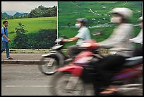 Man walking and motorbike riders blured in front of backdrops depicting traditional landscapes. Ho Chi Minh City, Vietnam (color)