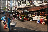Woman carrying goods on street market. Ho Chi Minh City, Vietnam (color)