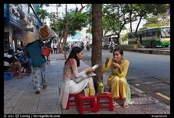 Women elegantly dressed in ao dai eating on the street. Ho Chi Minh City, Vietnam (color)