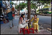 Women elegantly dressed in ao dai eating on the street. Ho Chi Minh City, Vietnam