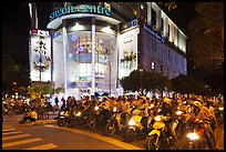 Dense motorcycle traffic in front of Saigon Center at night. Ho Chi Minh City, Vietnam (color)