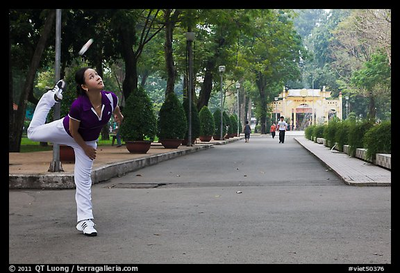 Woman plays badminton using feet (footbag), Tao Dan Park. Ho Chi Minh City, Vietnam (color)