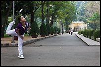 Woman plays badminton using feet (footbag), Cong Vien Van Hoa Park. Ho Chi Minh City, Vietnam (color)