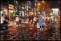 Traffic passes man pushing food cart on flooded street at night. Ho Chi Minh City, Vietnam ( color)