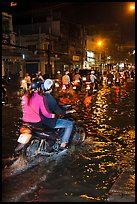Couple riding motorcycle on flooded street at night. Ho Chi Minh City, Vietnam ( color)