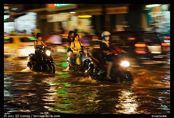 Women riding motorcyles at night in water. Ho Chi Minh City, Vietnam (color)
