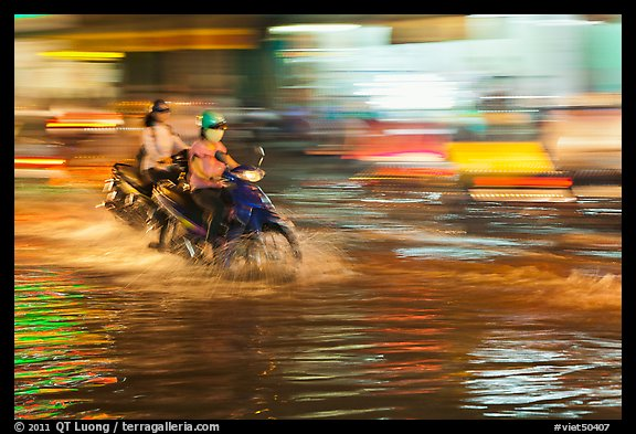 Motorcycle riders, water splashes, and streaks of light. Ho Chi Minh City, Vietnam (color)