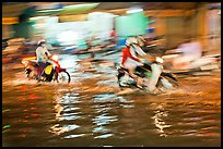 Motion-blured exposure of riders on flooded street at night. Ho Chi Minh City, Vietnam ( color)