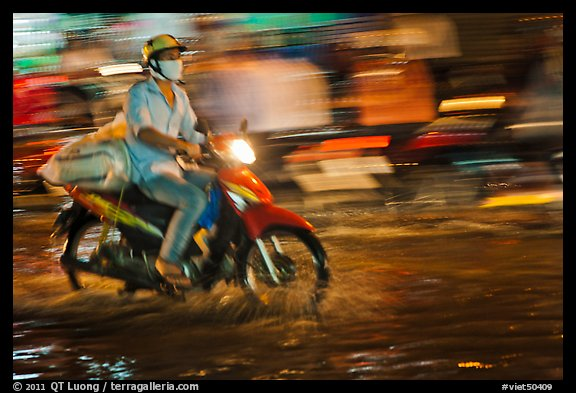 Motorcycle rider photographed with panning motion at night. Ho Chi Minh City, Vietnam (color)