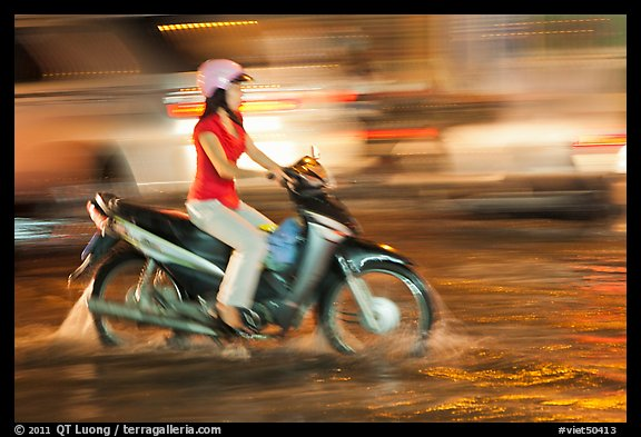 Woman riding on water-filled street, and light streaks. Ho Chi Minh City, Vietnam (color)