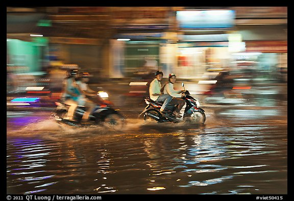 Motorcycles riding through the water on street with motion. Ho Chi Minh City, Vietnam (color)