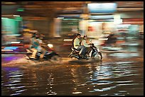 Motorcycles riding through the water on street with motion. Ho Chi Minh City, Vietnam ( color)
