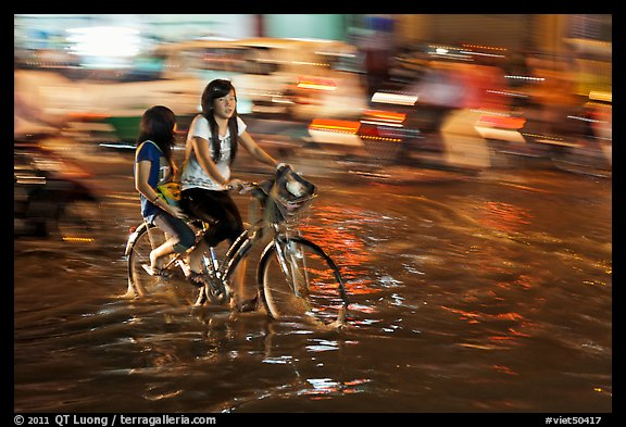 Girls sharing night bicycle ride through water of flooded street. Ho Chi Minh City, Vietnam (color)