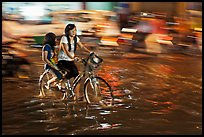 Girls sharing night bicycle ride through water of flooded street. Ho Chi Minh City, Vietnam