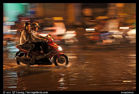 Couple sharing fast night ride on wet street. Ho Chi Minh City, Vietnam (color)