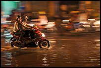 Couple sharing fast night ride on wet street. Ho Chi Minh City, Vietnam ( color)