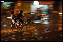 Men sharing bicycle ride at night on wet street. Ho Chi Minh City, Vietnam (color)