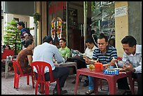 Men eating breakfast on the street. Ho Chi Minh City, Vietnam (color)