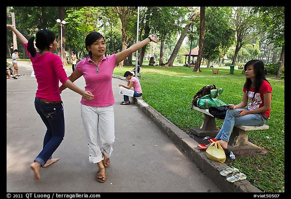Young women dancing to sound of mobile phone, Tao Dan Park. Ho Chi Minh City, Vietnam (color)