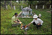 Women burning notes as offering in cemetery. Ben Tre, Vietnam