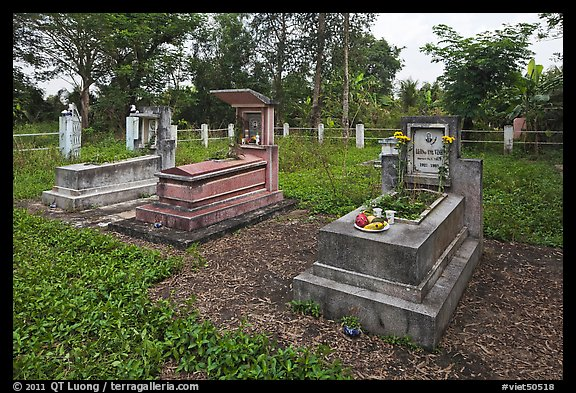 Graves in family cemetery with fresh offerings. Ben Tre, Vietnam (color)